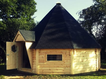A 25m² camping cabin on a field with it's door open.