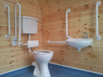 A toilet beside a sink inside a camping pod.
