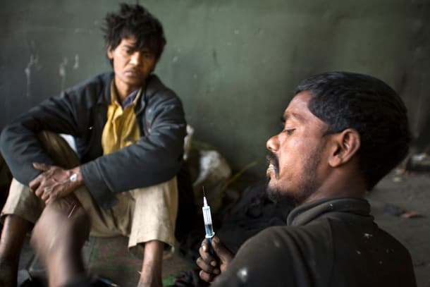 India - Homelessness New Delhi - Homeless addicts prepare and inject heroin