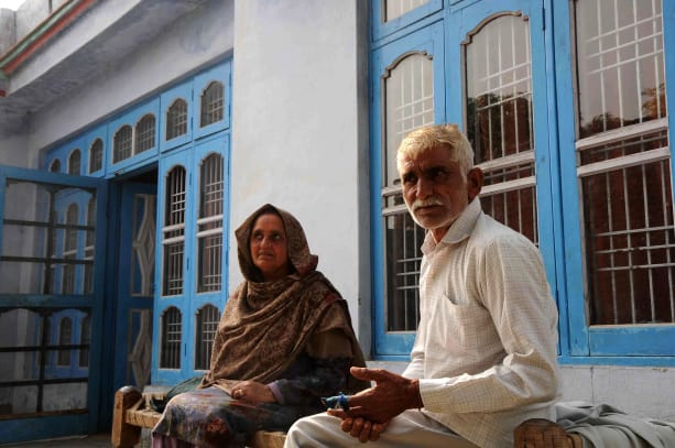 Kamal Nath and his wife sitting on Charpai in the courtyard of their house in Palatan