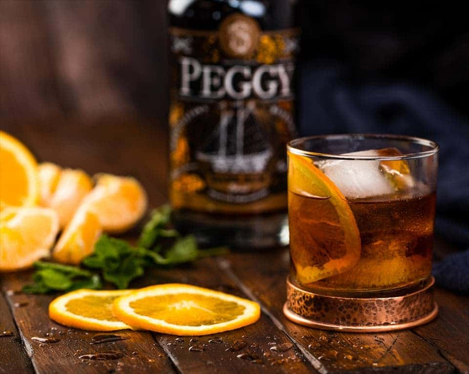 A glass of Peggy rum on a table