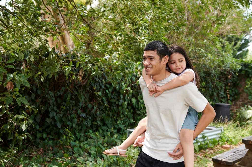 Youth piggybacking girl in garden