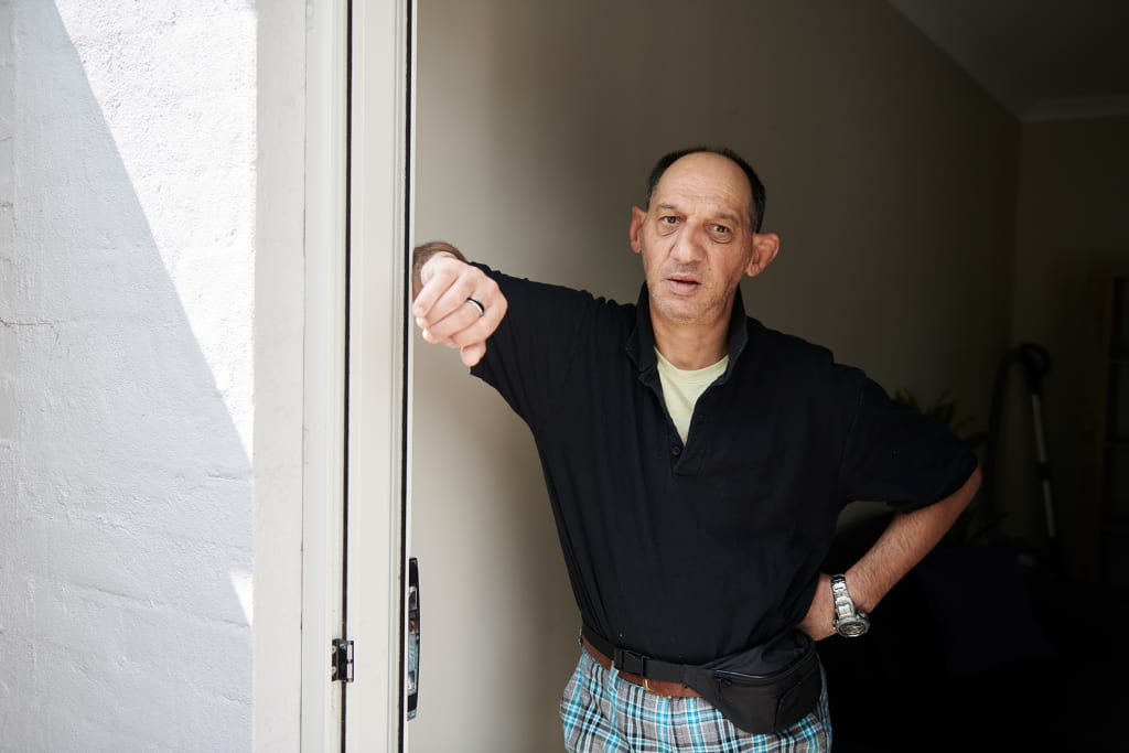 Man in black t-shirt leaning against a door