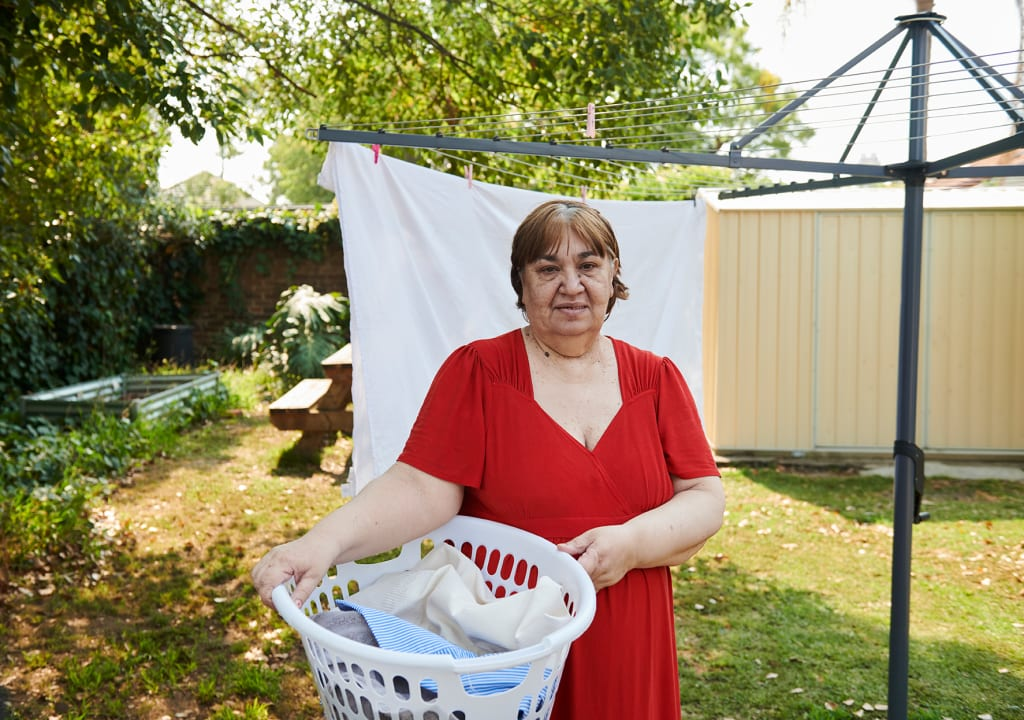 Lady in red dress with washing basket at line