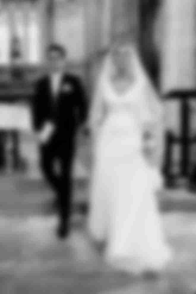 Un marié en costume sur mesure bleu foncé qui tient la main de sa femme dans l'église