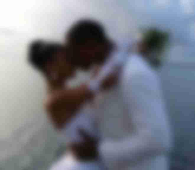 Marié en costume blanc sur mesure Atelier Mesure qui embrasse sa femme devant l'océan