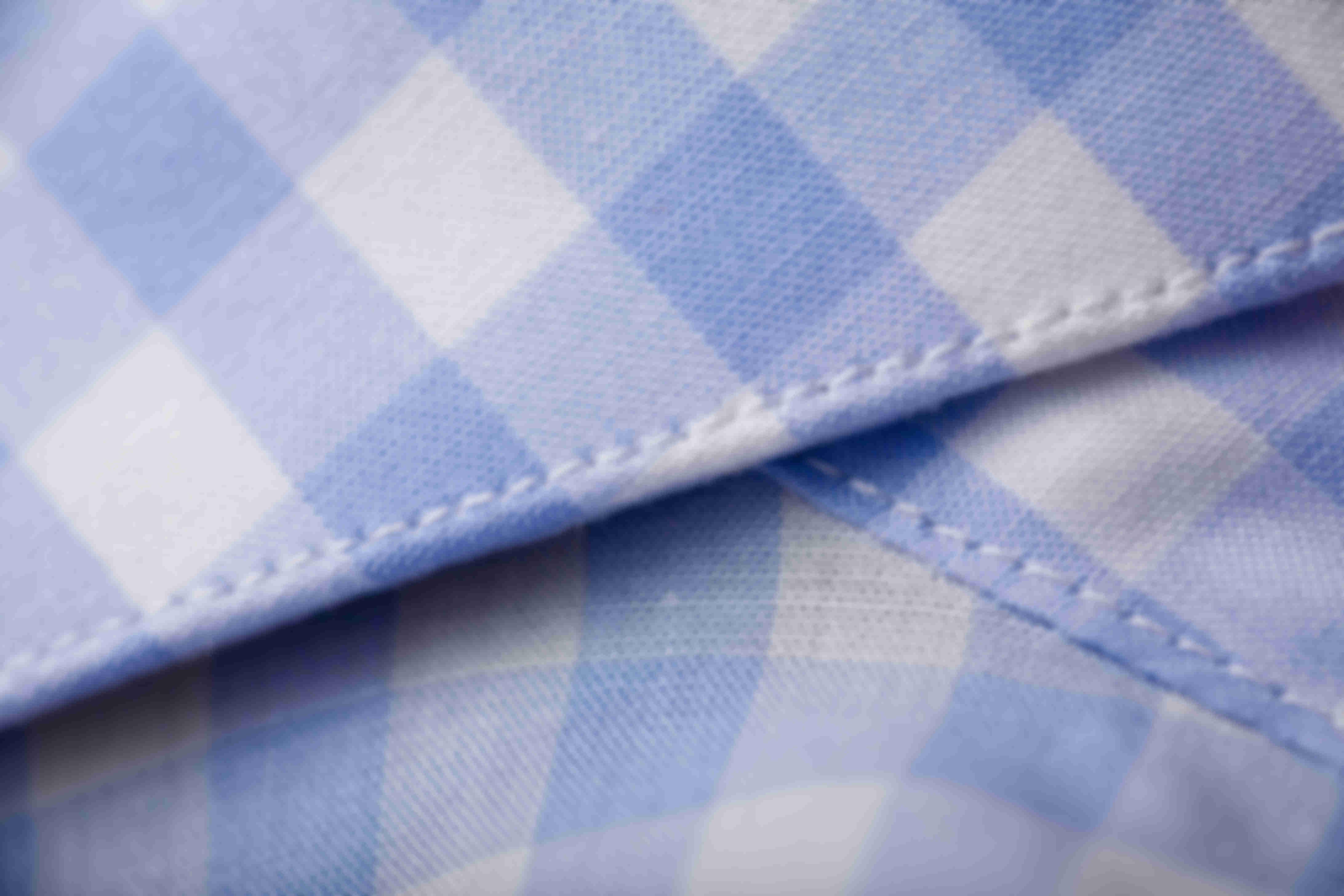Zoom sur la densité de couture avec 9 points de piqûres par centimètre sur les chemises sur mesure Atelier Mesure