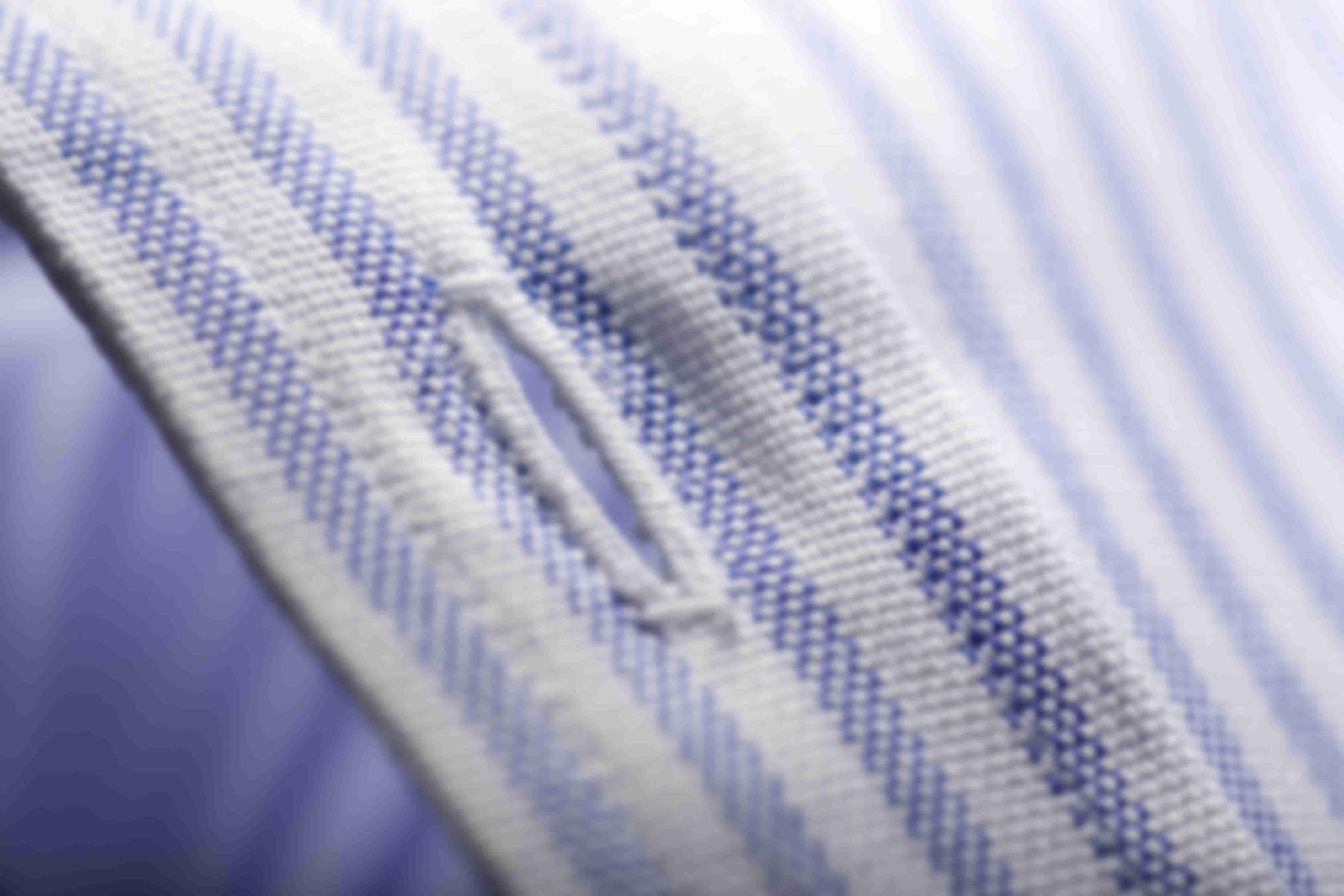 Zoom sur la fabrication à la main de toutes les boutonnières des chemises sur mesure Atelier Mesure