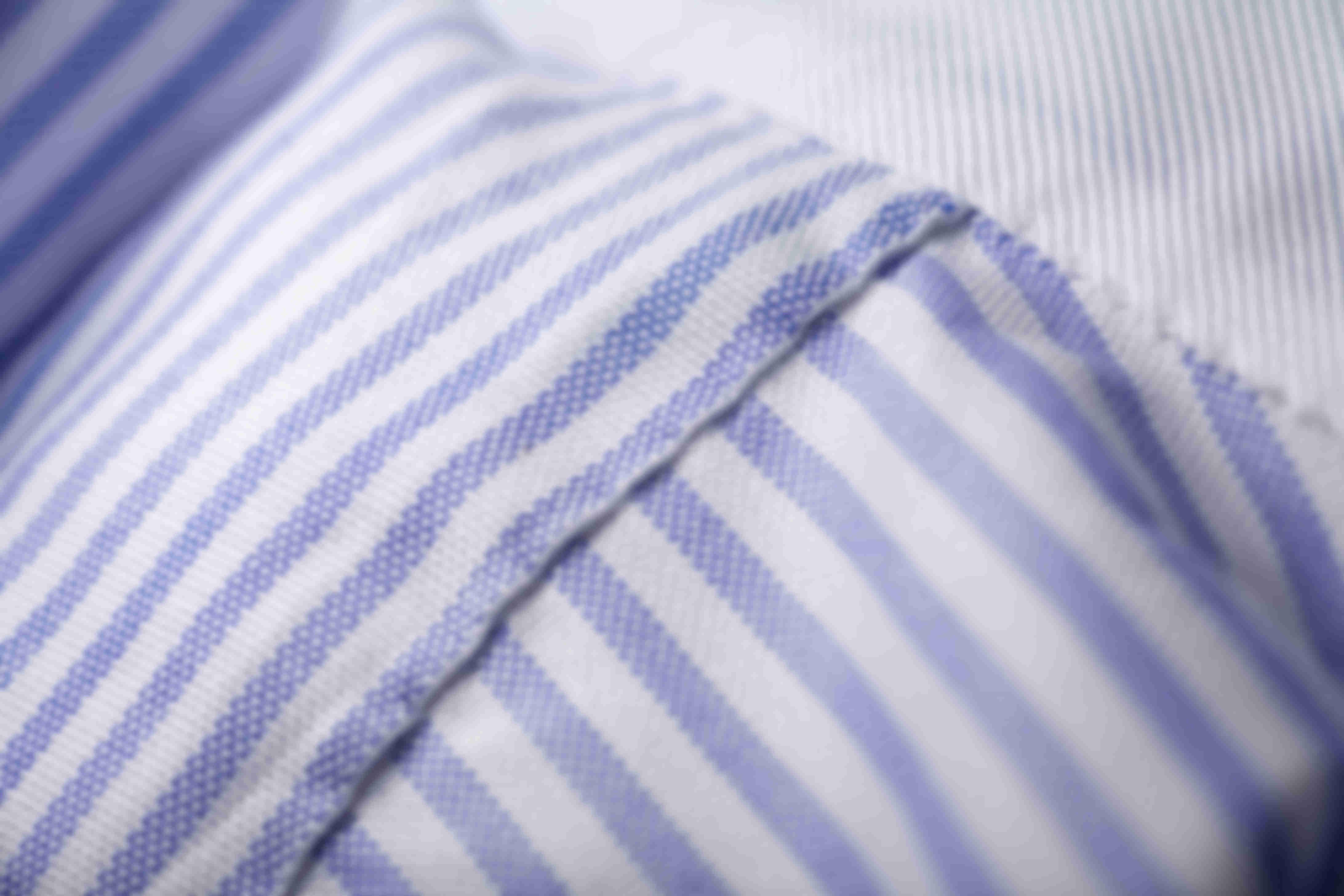 Zoom sur la fabrication à la main de l'empiècement du dos des chemises sur mesure Atelier Mesure