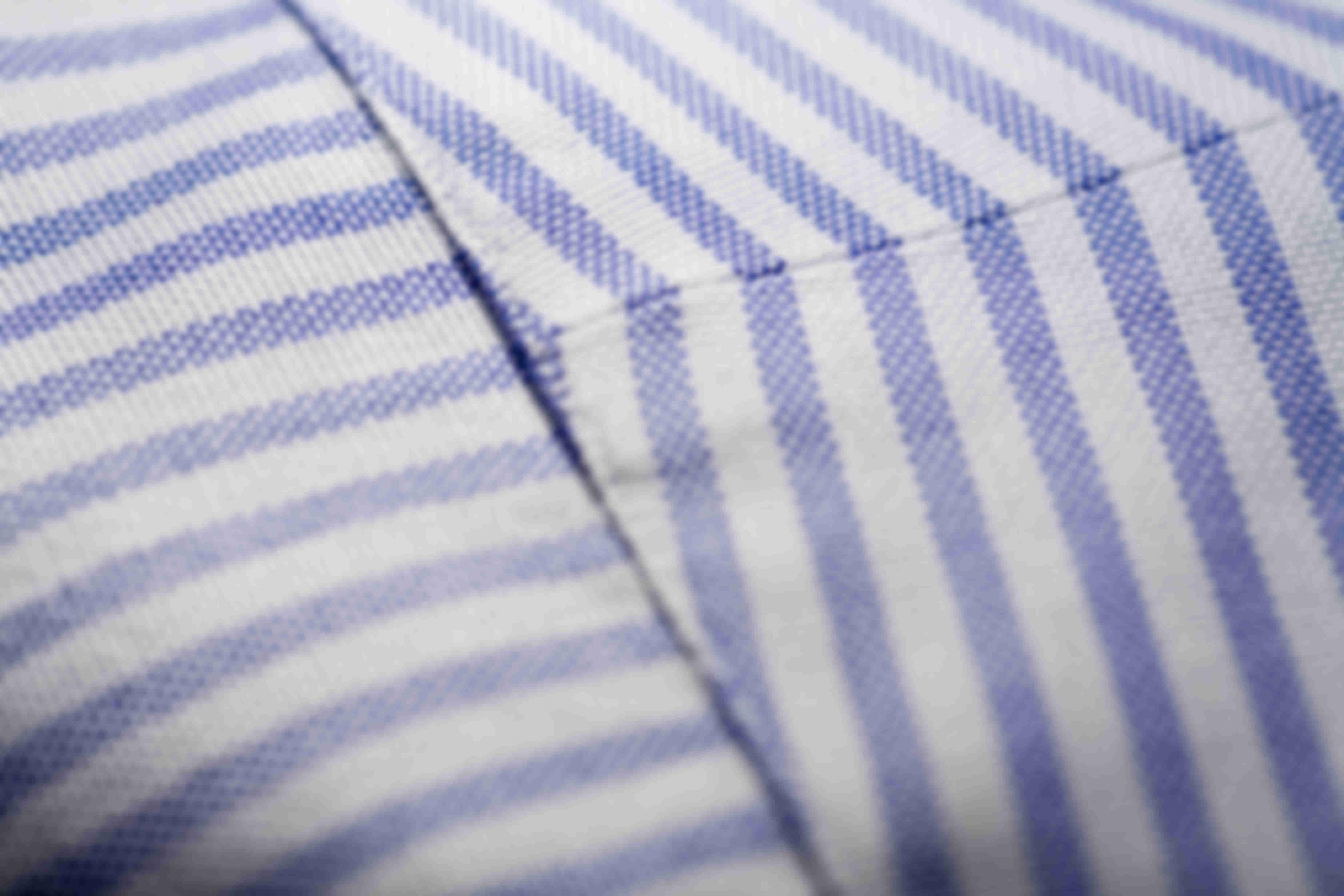Zoom sur la fabrication à la main de l'empiècement de dos en deux parties des chemises sur mesure Atelier Mesure