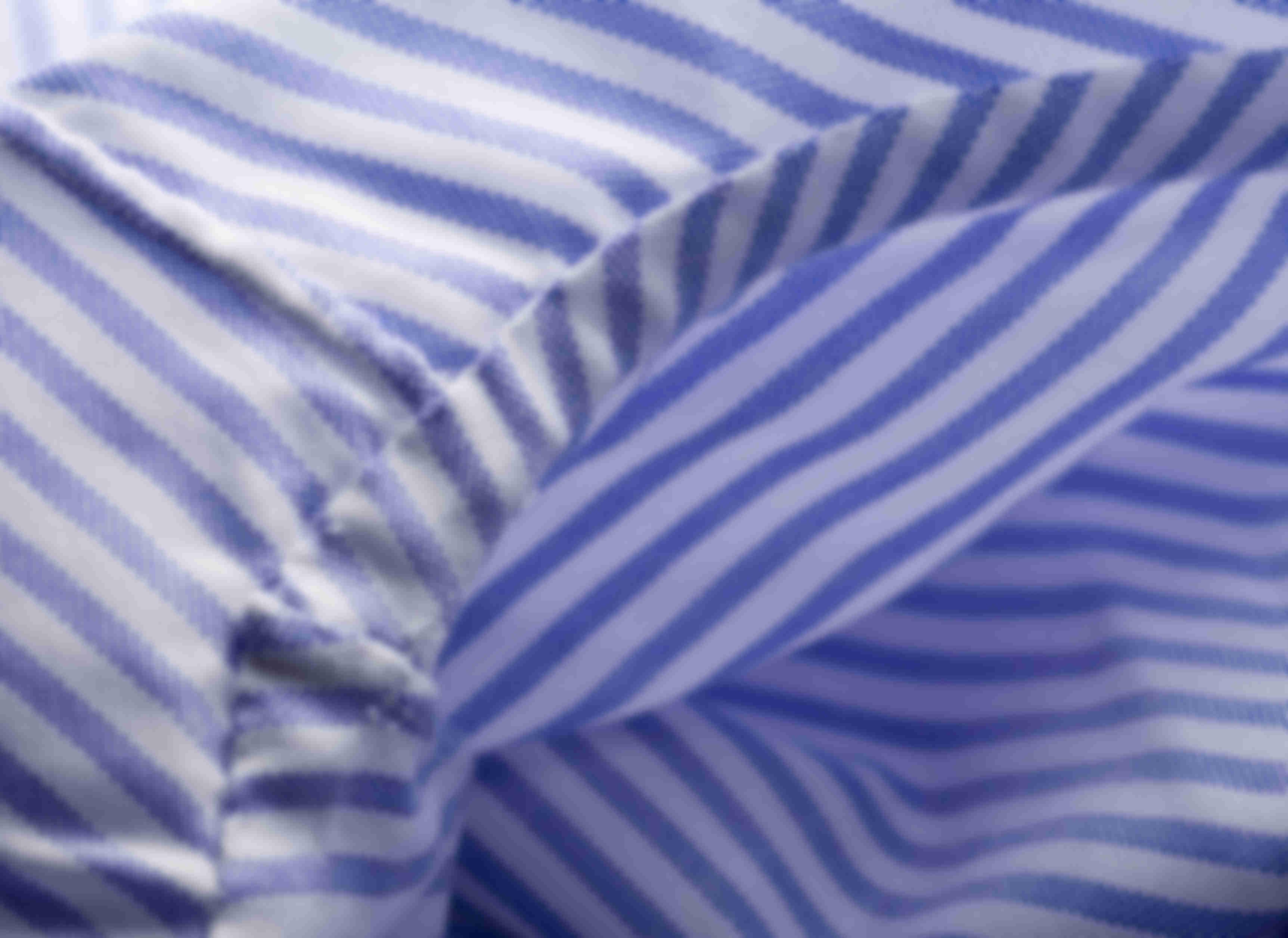 Zoom sur la fabrication à la main de la fixation des manches des chemises sur mesure Atelier Mesure