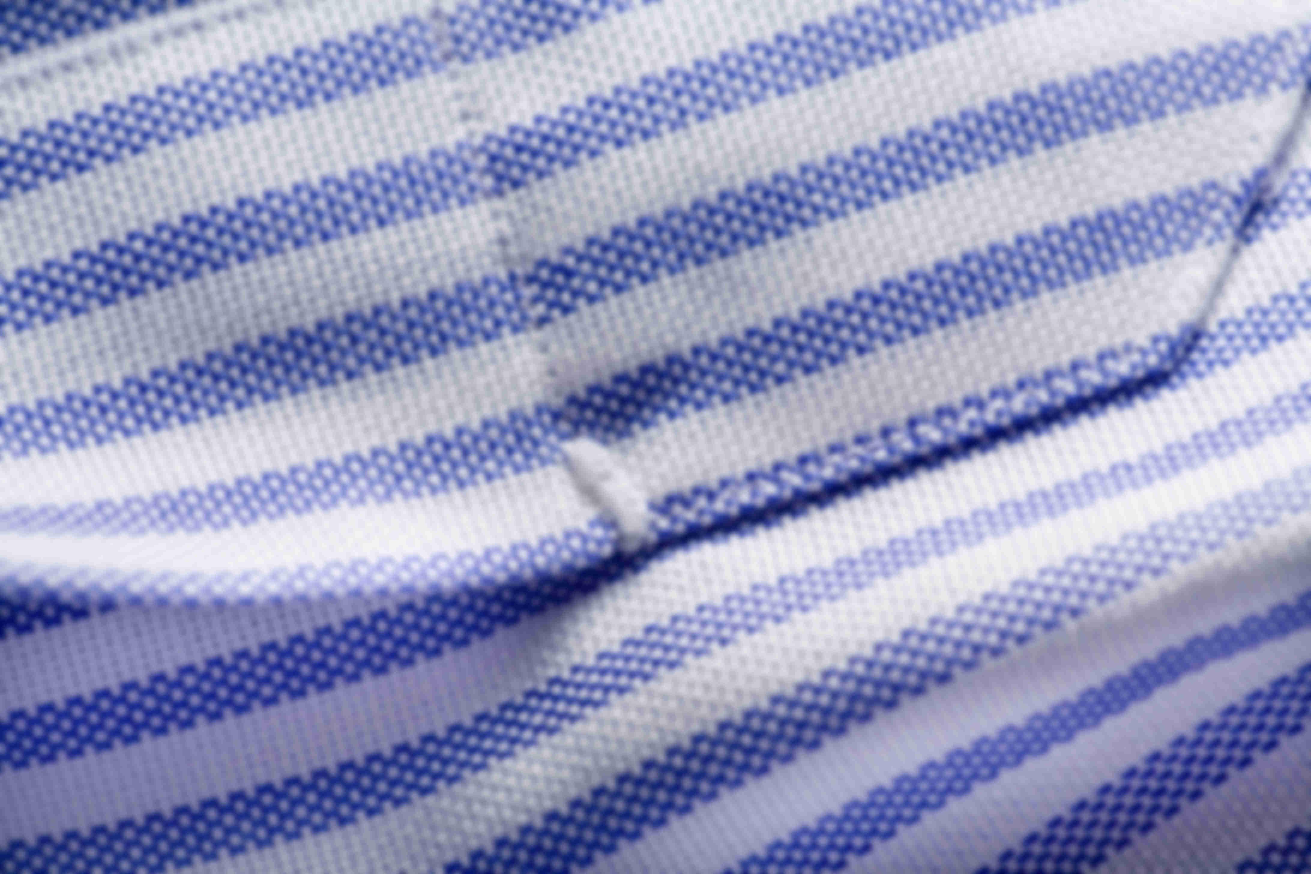 Zoom sur la fabrication à la main des points d'arrêt au niveau de la patte capucin sur les chemises sur mesure Atelier Mesure