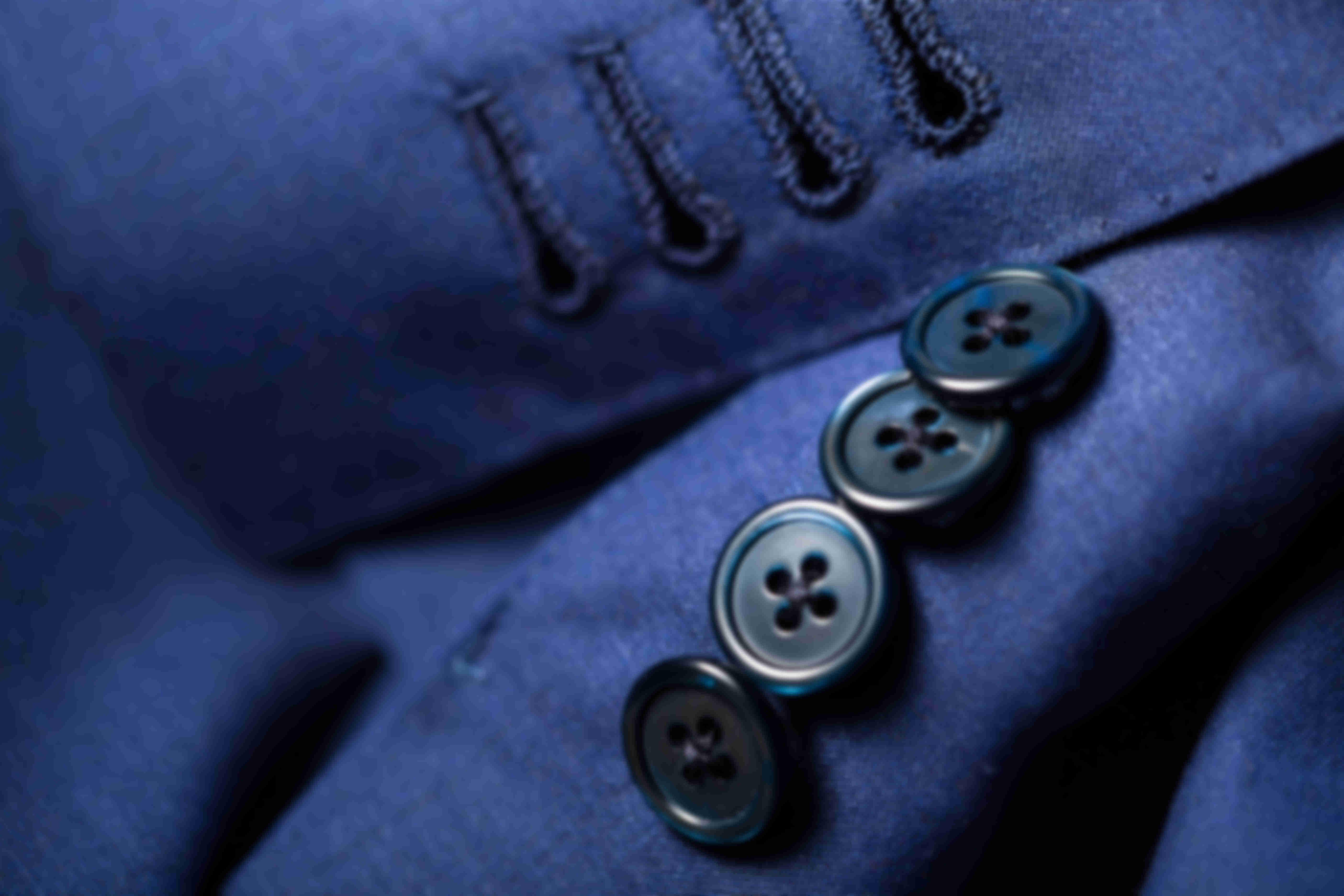 Zoom sur les boutonnières veste ouvertes faites main sur les vestes Atelier Mesure