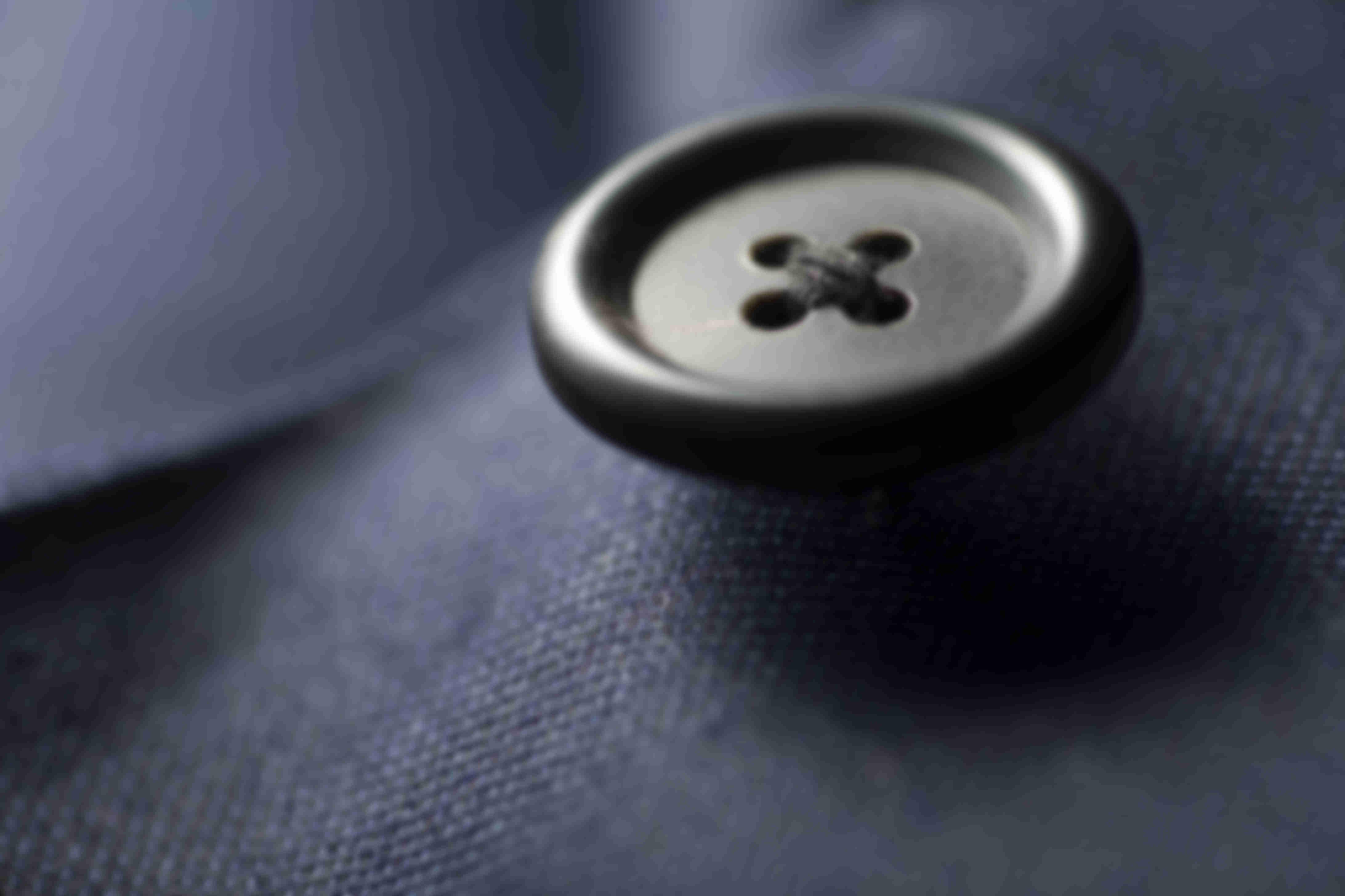 Zoom sur la fabrication des coutures en croix sur les boutons cornes des vestes Atelier Mesure