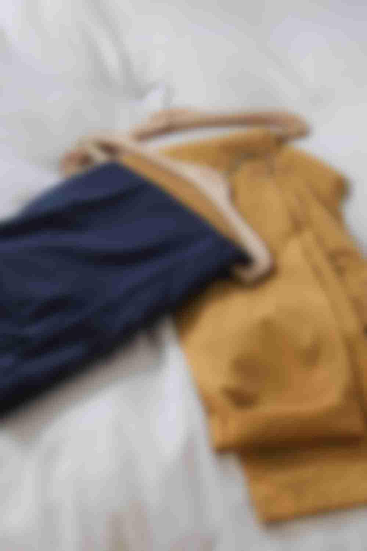 Chino bleu et moutarde sur mesure sur un lit