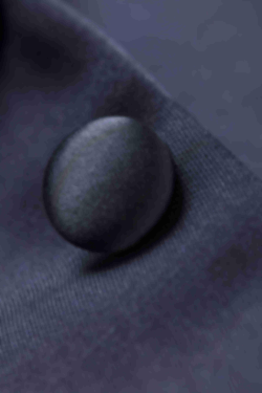 Zoom sur un bouton gansé du même tissu que le costume de mariage sur mesure