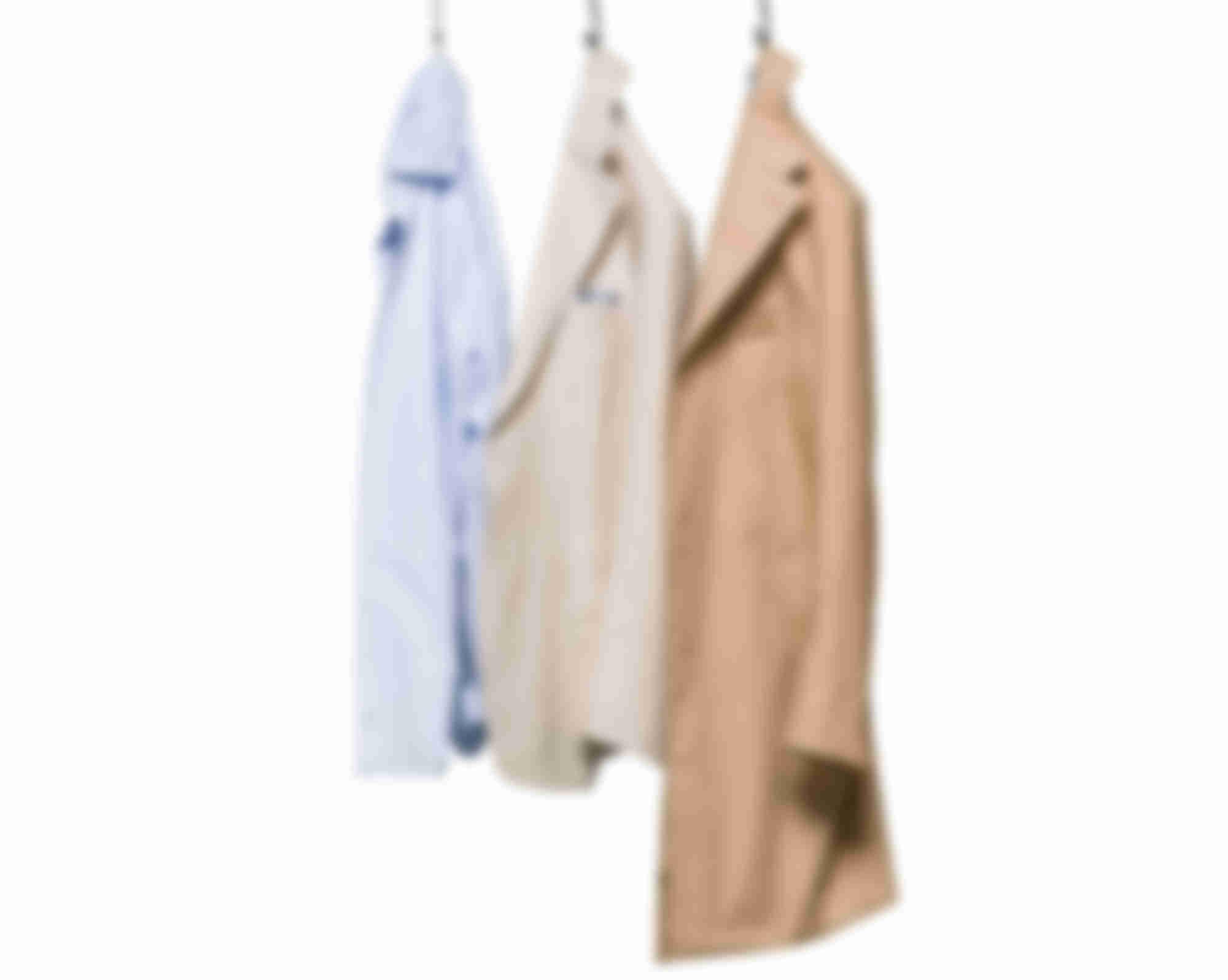 Chemise veste et manteaux suspendus qui illustrent la philosophie Sur-Mesure