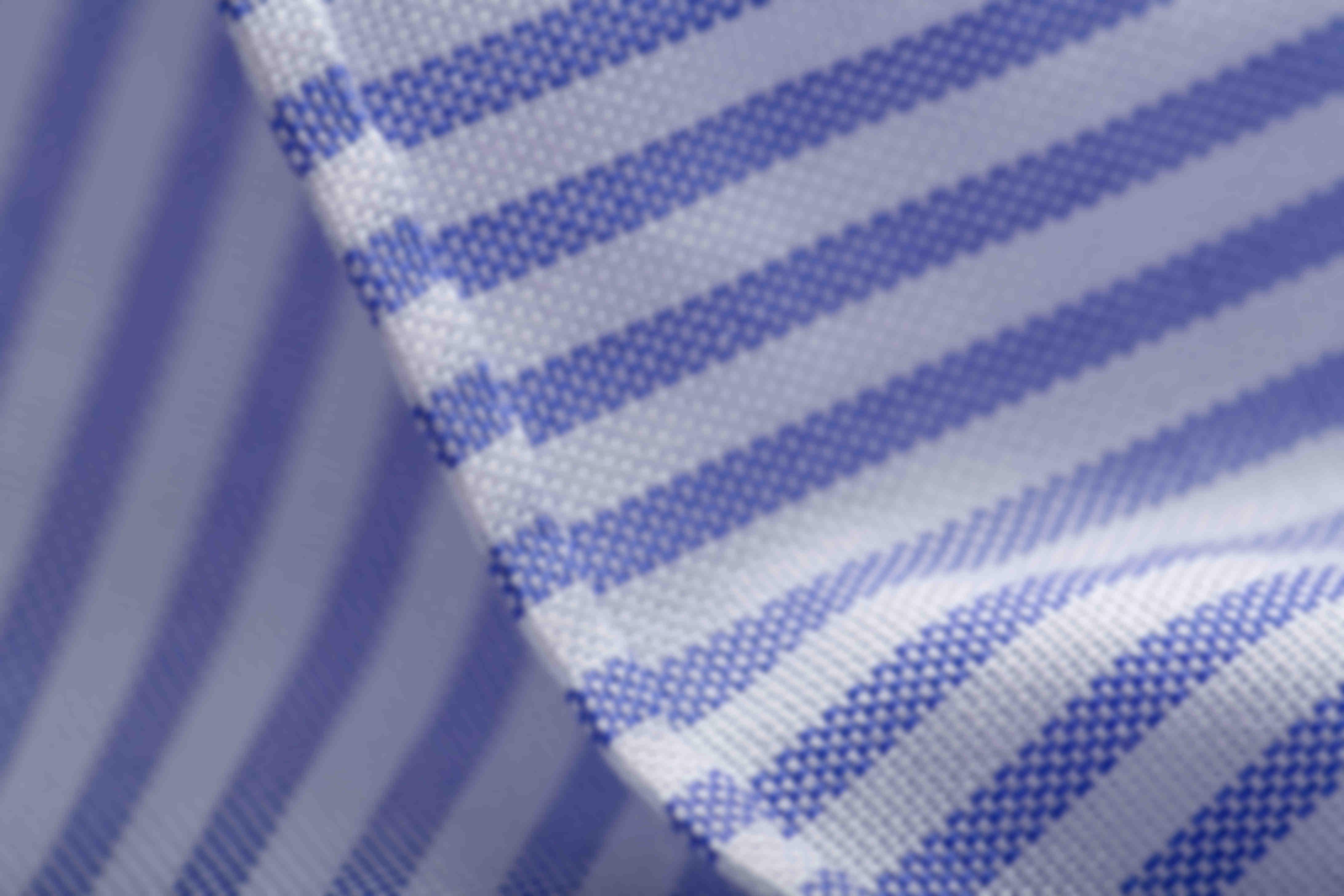 Zoom sur la fabrication à la main de l'ourlet roulotté en bas des chemises sur mesure Atelier Mesure