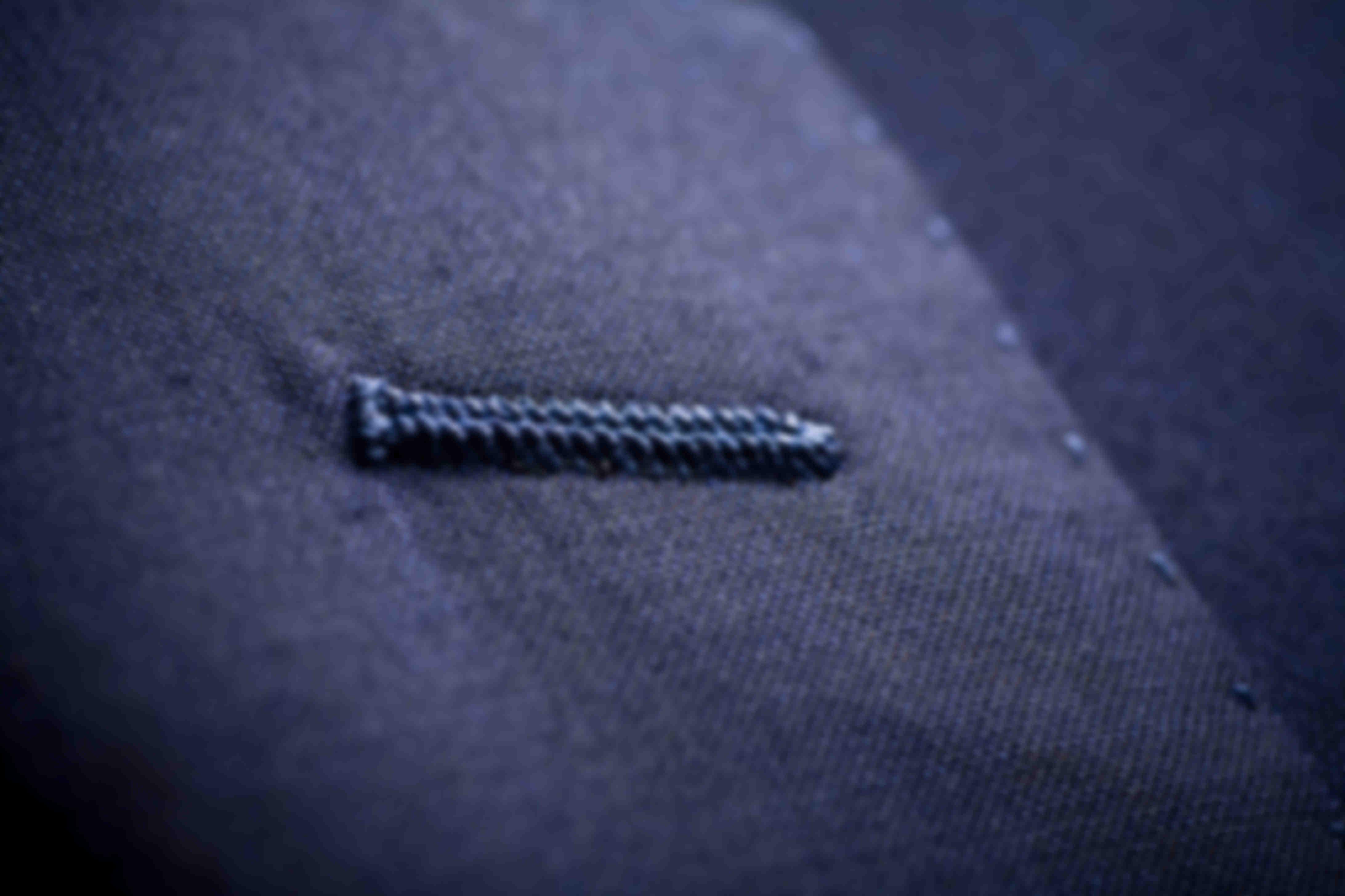 Zoom sur la fabrication à la main des boutonnières de revers sur les vestes sur mesure Atelier Mesure