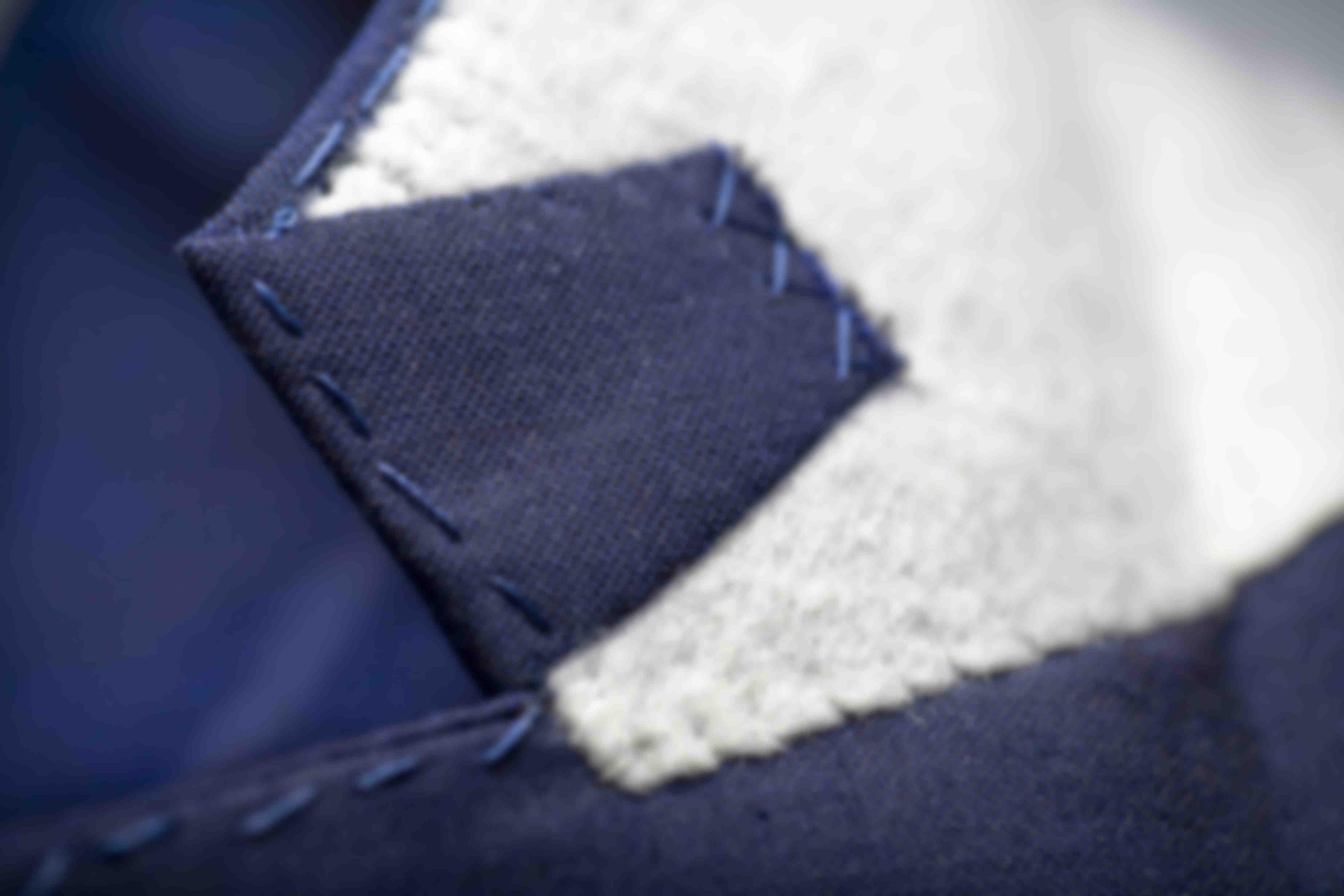 Détail de fabrication du retour d'une patte en tissu dessous le col cousue main