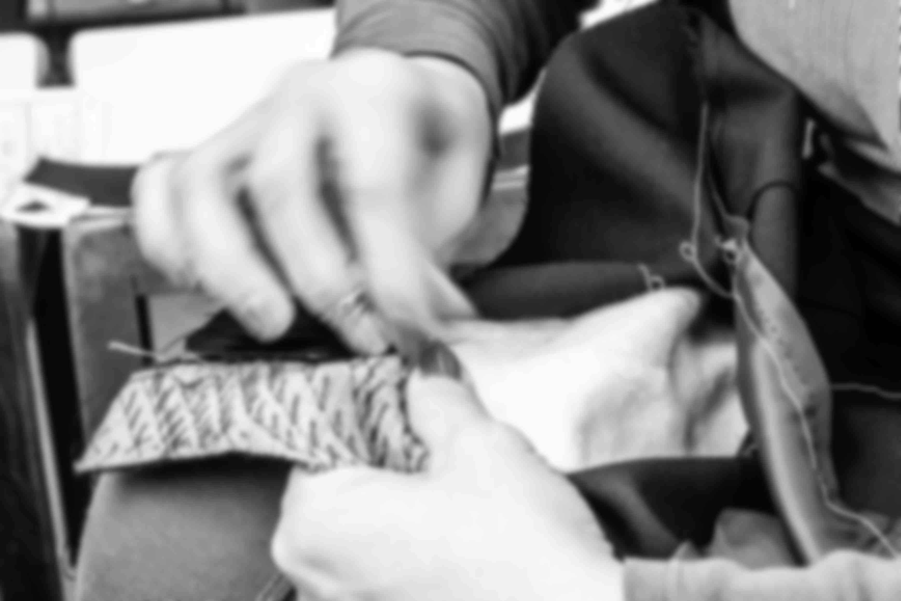 Main qui pique un plastron de veste de manière tailleur pour illustrer la construction traditionnel fait main des costumes et vestes sur-mesure Atelier Mesure