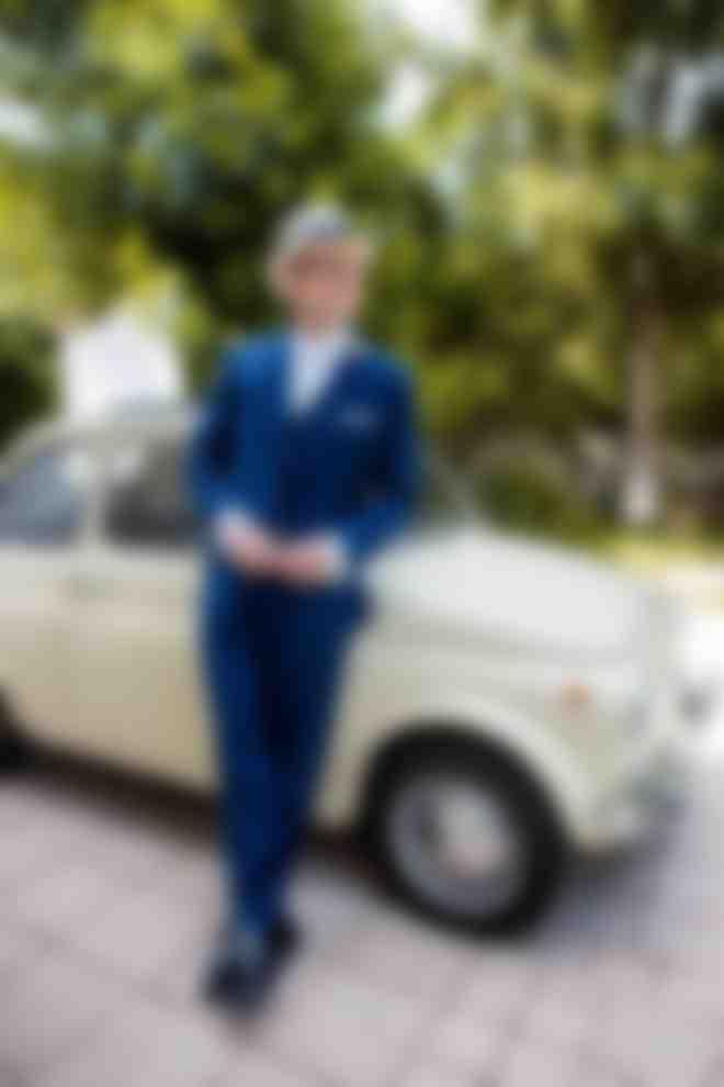 Un marié en costume 3 pièces bleu roi Atelier Mesure appuyé sur une voiture de collection