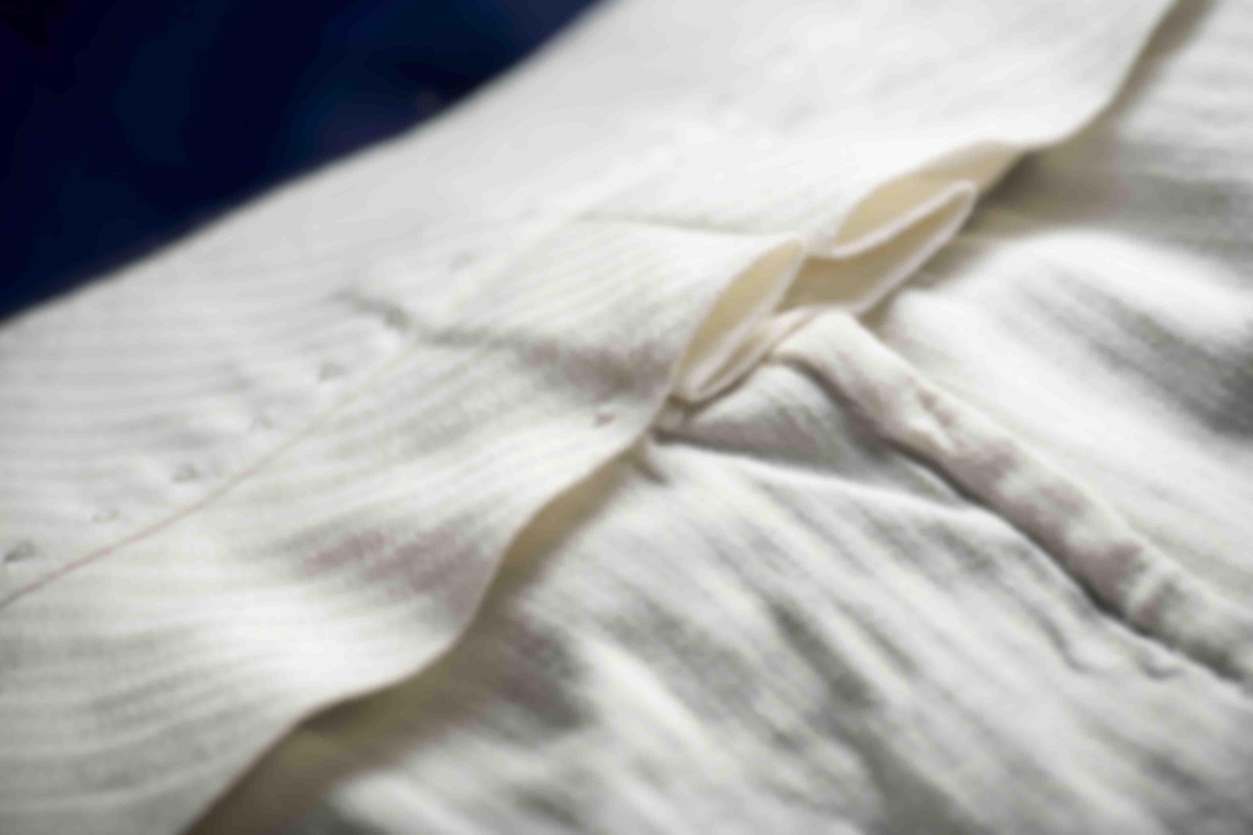 Zoom sur la fabrication à la main des hausses de ceinture plissées sur les pantalons sur mesure Atelier Mesure