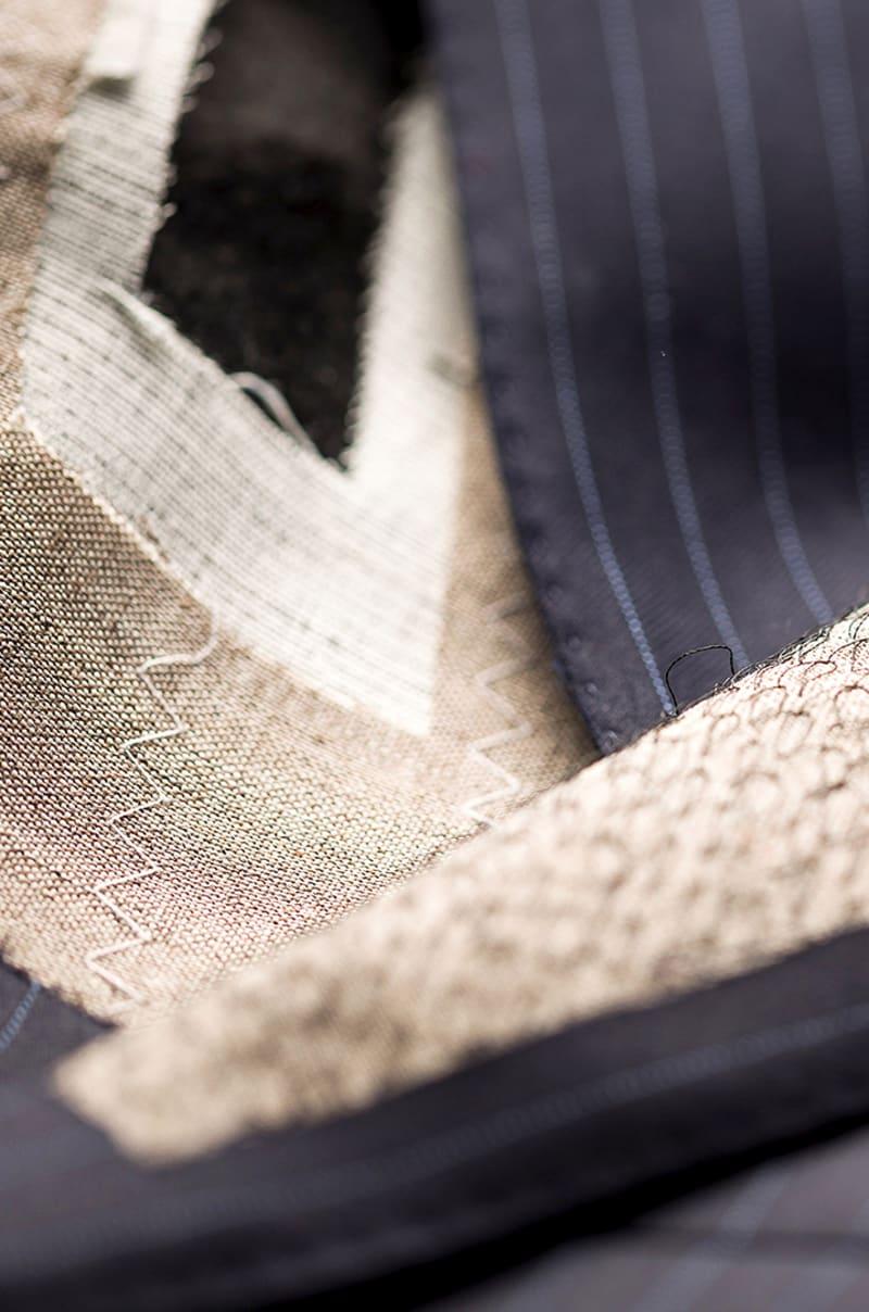 Veste démontée qui laisse voir l'entoilage tailleur et les points de piqûres du plastron