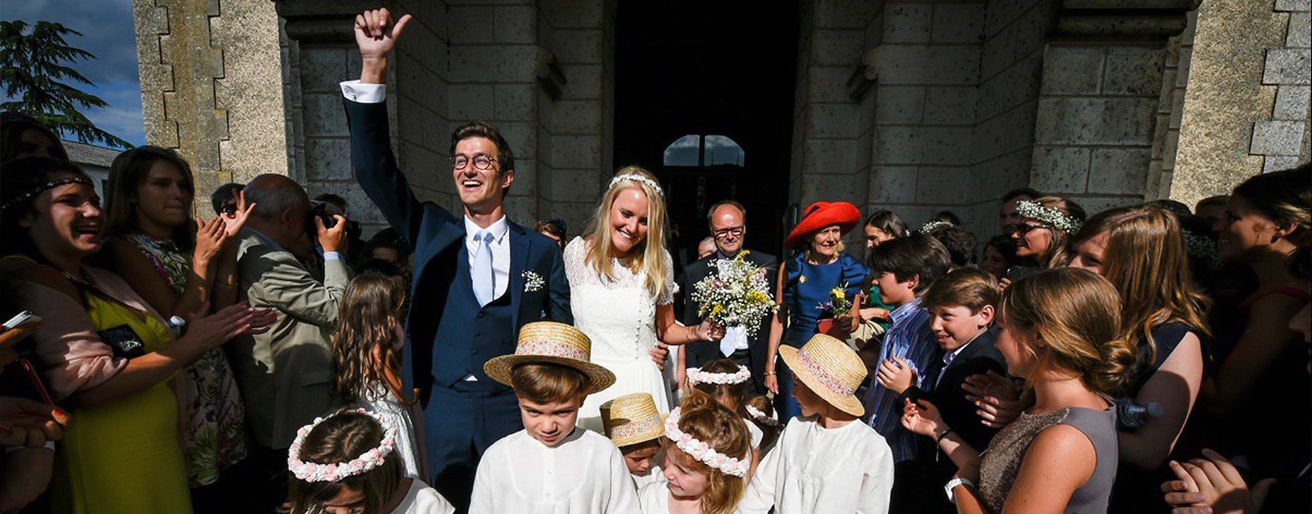 Un marié en costume sur mesure bleu Atelier Mesure et sa femme lors de leur sortie de l'église