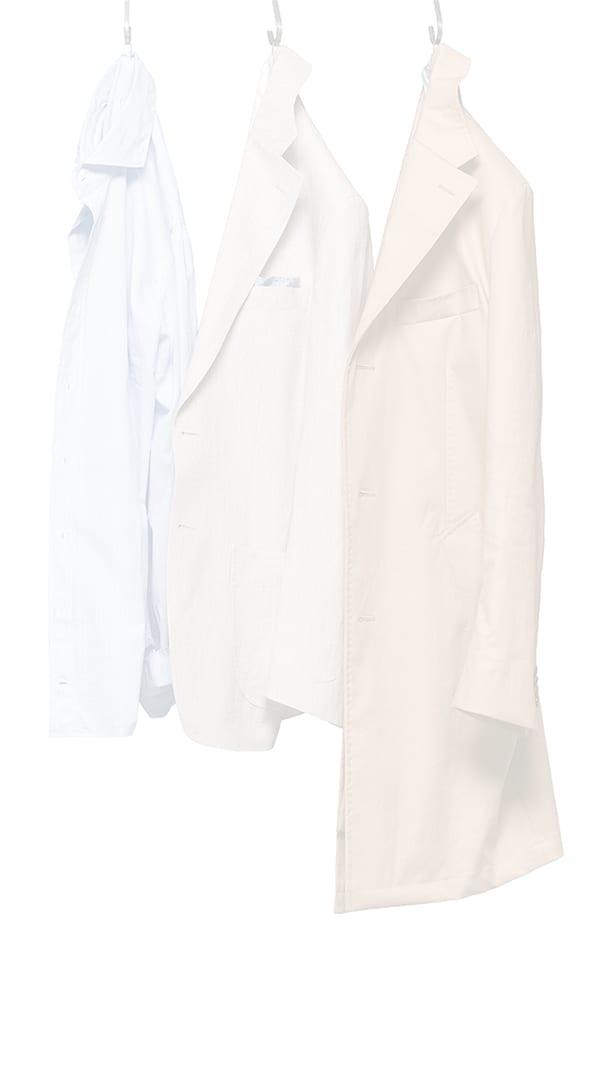 Une chemise bleue, une veste déconstruite beige et un manteau fauve suspendus, de la marque Atelier Mesure
