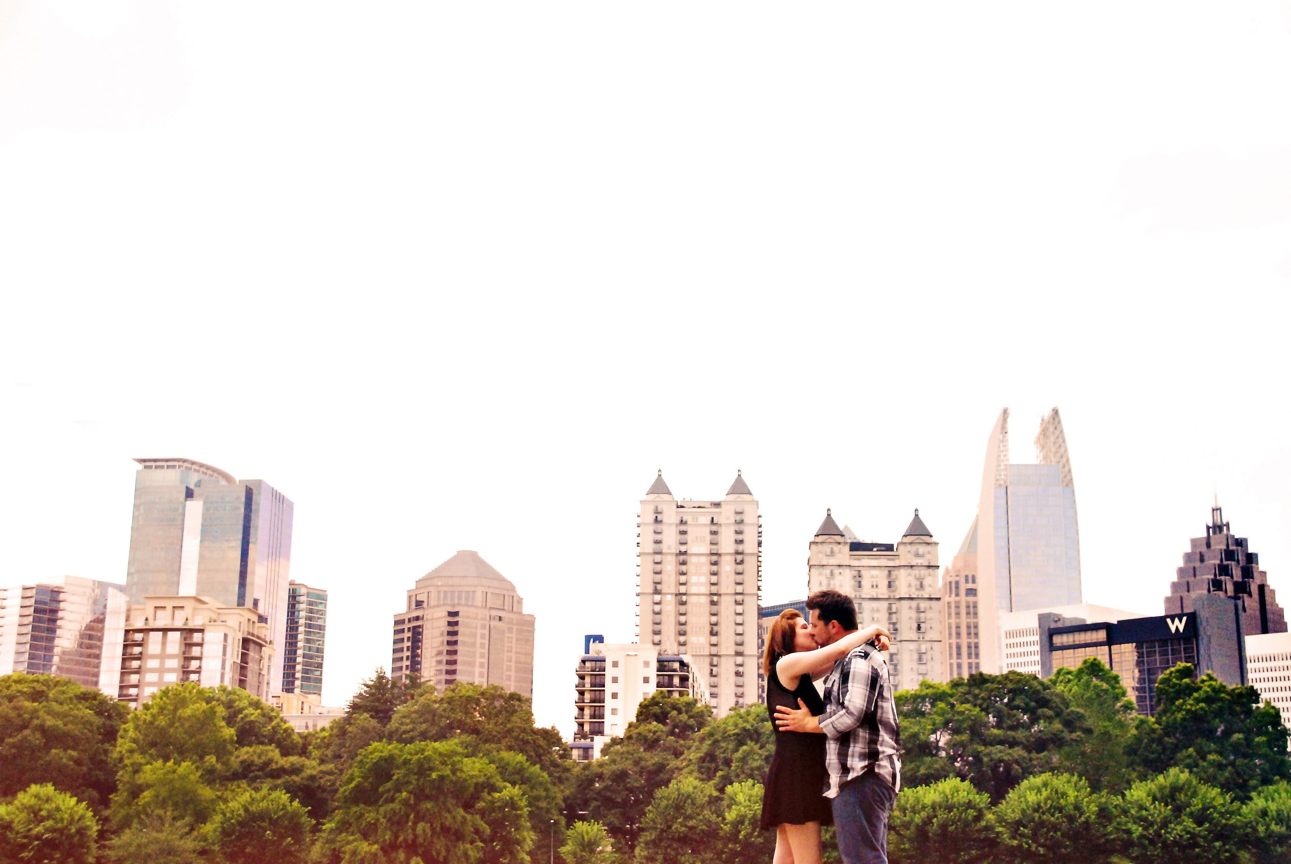 Couple kissing in Piedmont Park with the Atlanta skyline behind them.