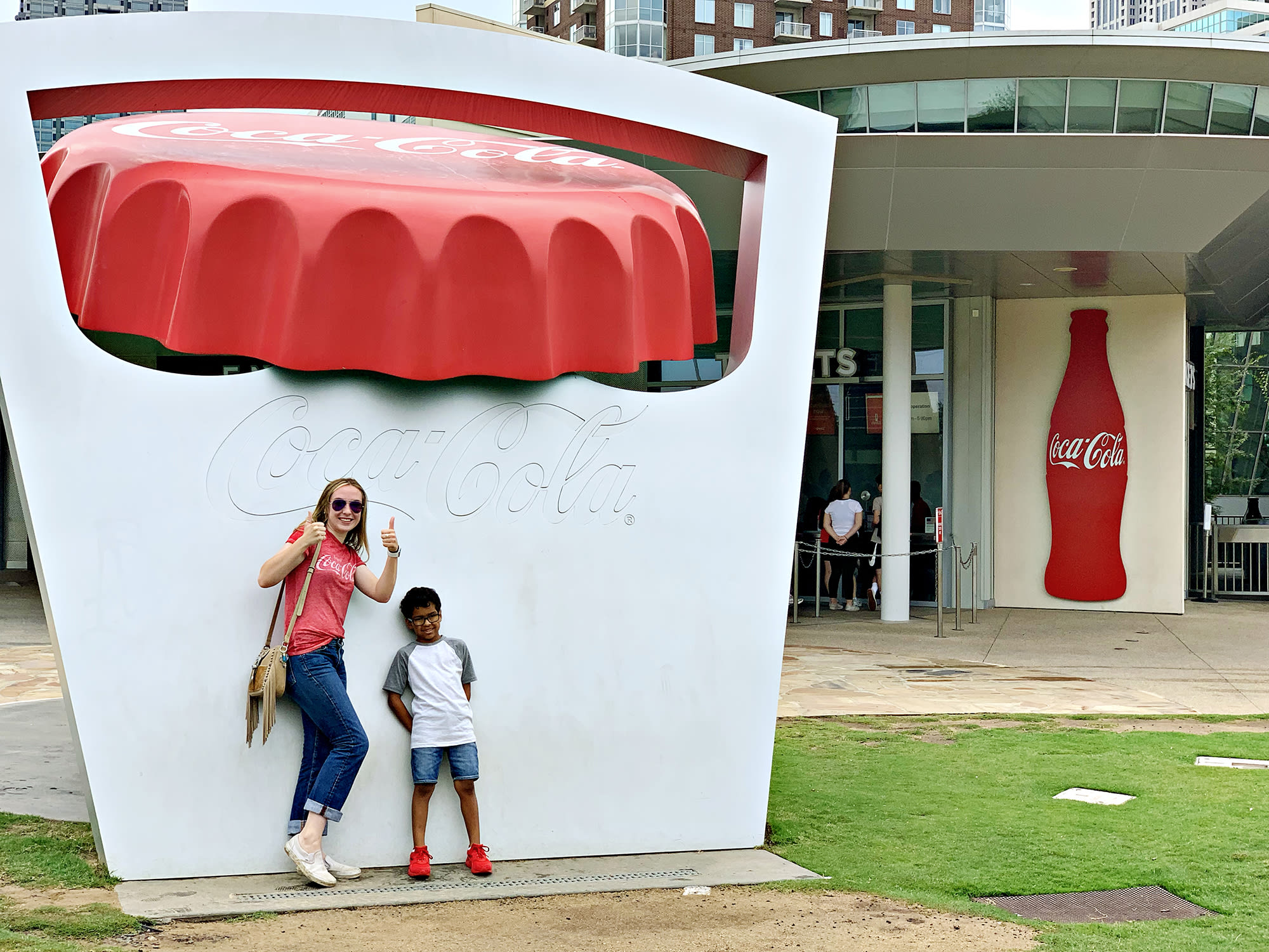 Family friends posing in front of the giant Coca-Cola cap sign before going into World of Coca-Cola.