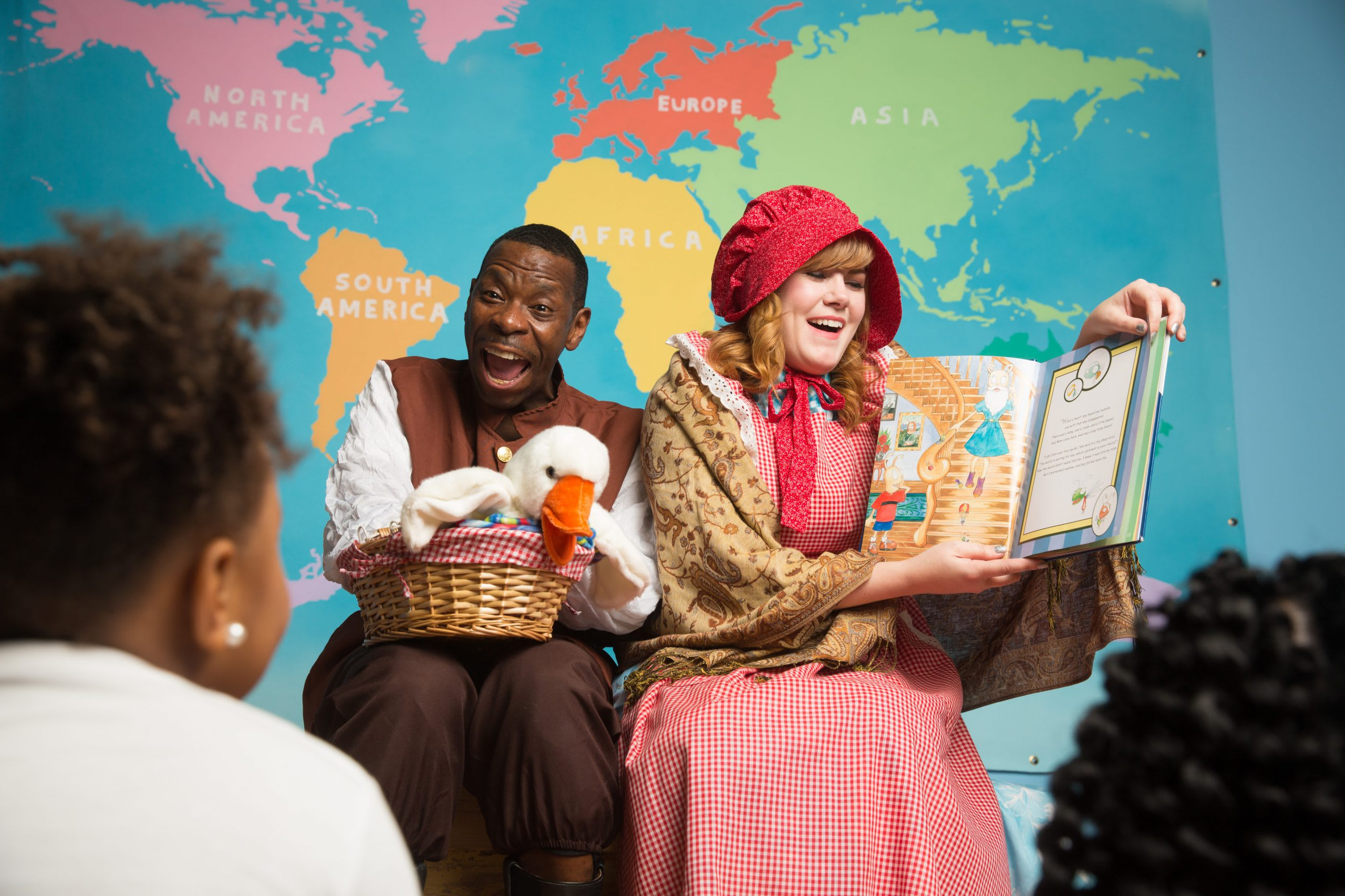 Two animated adults telling a story to children at the Children's Museum of Atlanta.