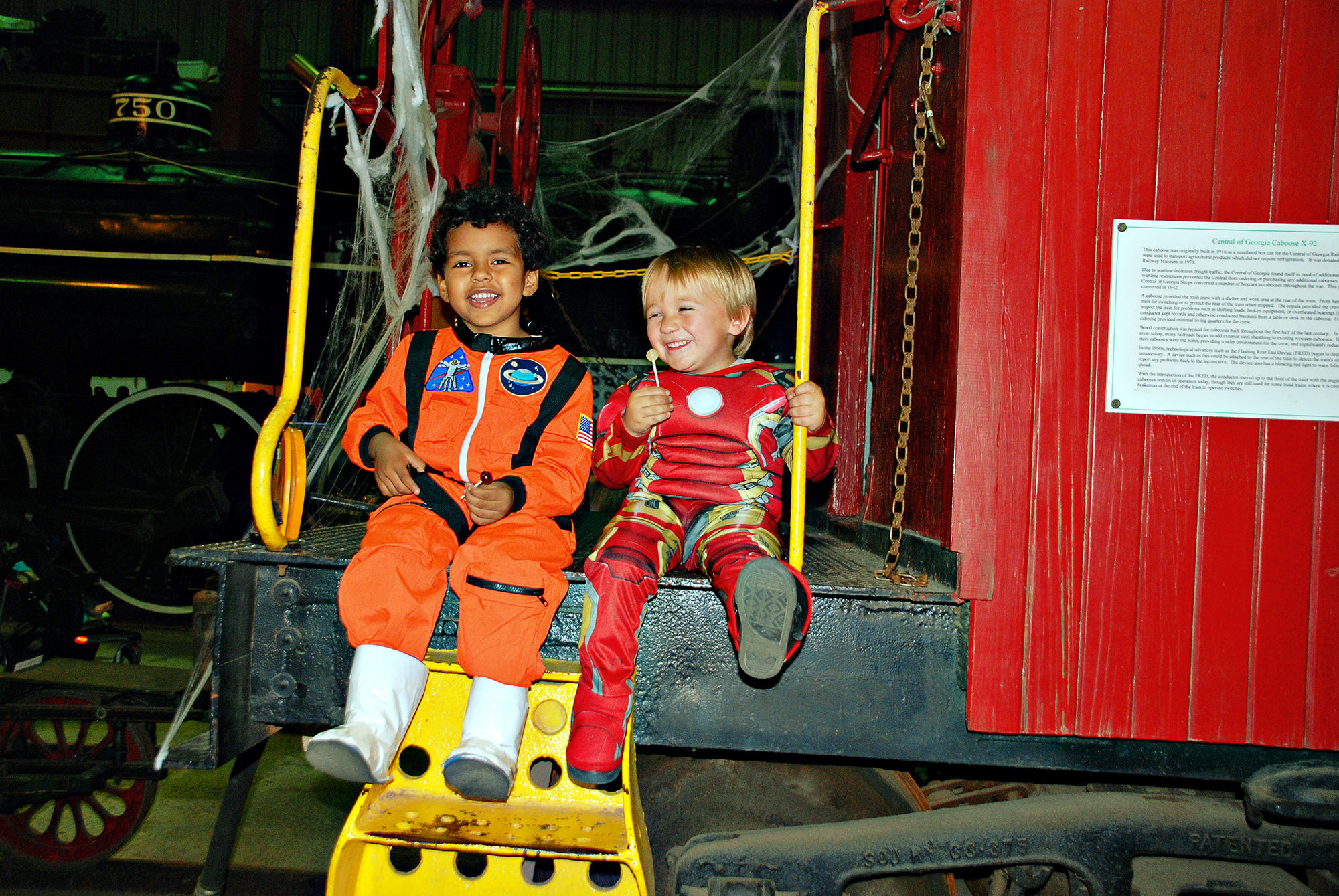 Two boys sit and laugh on the end of a train caboose, while dressed in costumes and eating candy, at Train or Treat - an annual Halloween event at Southeastern Railway Museum.