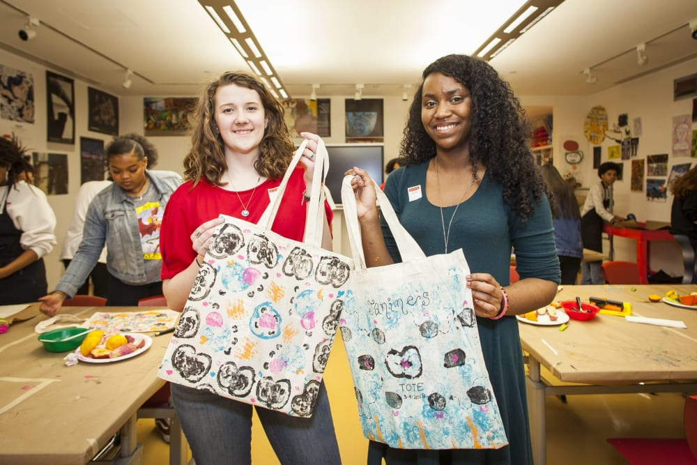Two teen girls holding up tote bags they printed during Teen Night at the High Museum of Art Atlanta.