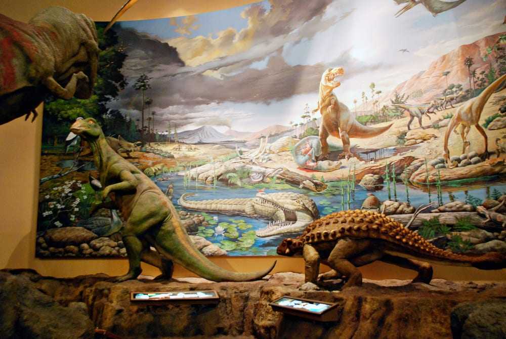 Three dinosaur statues stand in front of a painting of a scene in an exhibit at Fernbank Museum of Natural History in Atlanta Georgia.