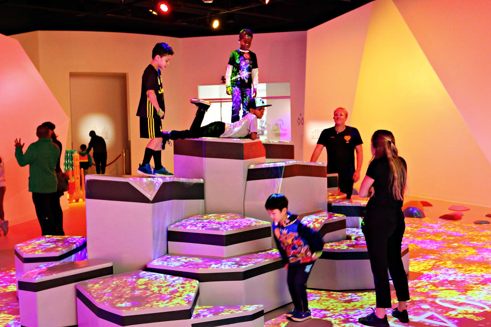 Kids climb, jump, and lay on padded blocks, guided by Playsmiths at a play space in Buckhead, called Kefi.