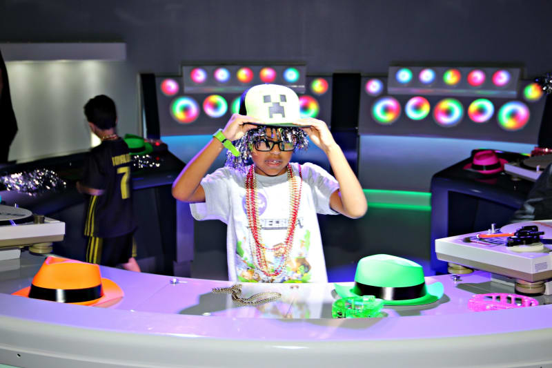 A boy holds onto his Minecraft hat and listens to music, as he enjoys his birthday party at Kefi - an indoor play space for kids in Buckhead Atlanta.
