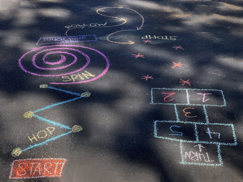 A sidewalk obstacle course drawn in chalk, that includes prompts like hop, spin, follow, stomp, and turn.