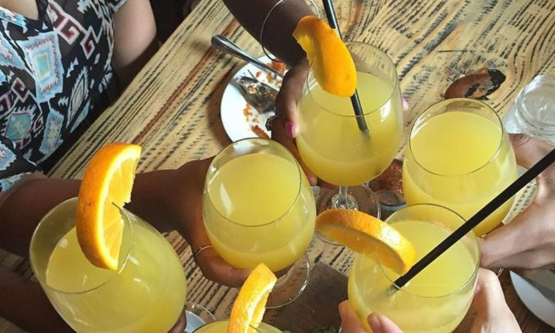 Friends toast mimosas at brunch at Meehan's Public House.