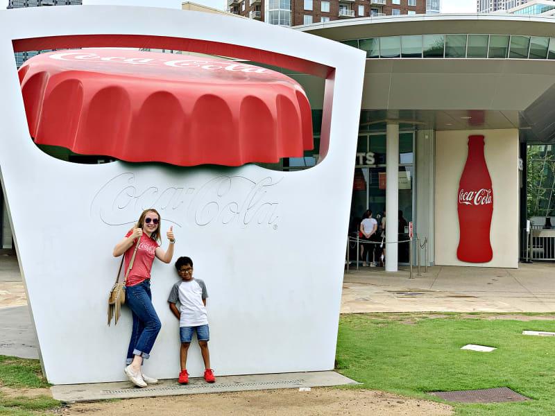 Family friends pose in front of a large Coca-Cola cap statue outside World of Coca-Cola in Atlanta, Georgia.