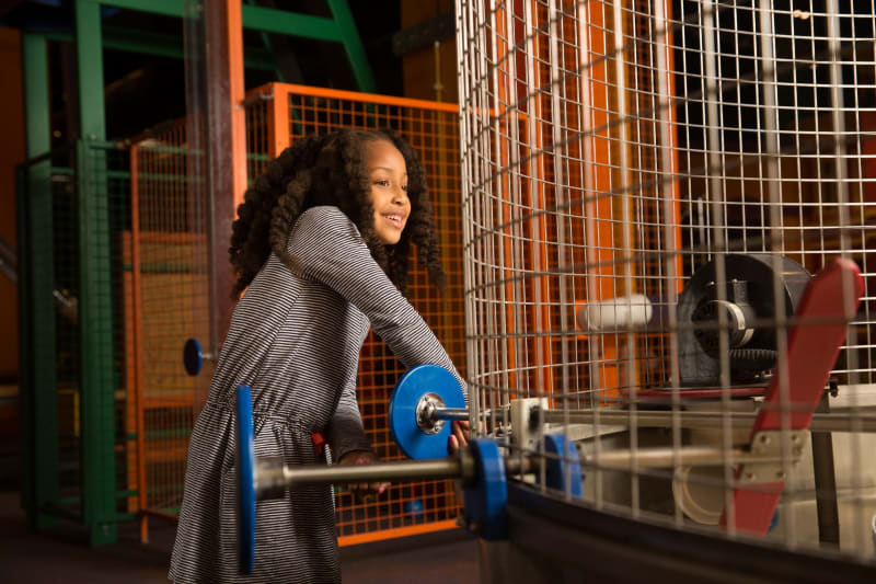 A happy girl turns a machine to move ping pong balls around a STEAM-focused activity at the Children's Museum of Atlanta.