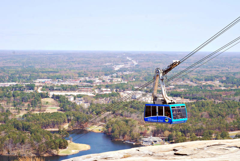 A blue Summit Skyride tram makes its way down Stone Mountain.