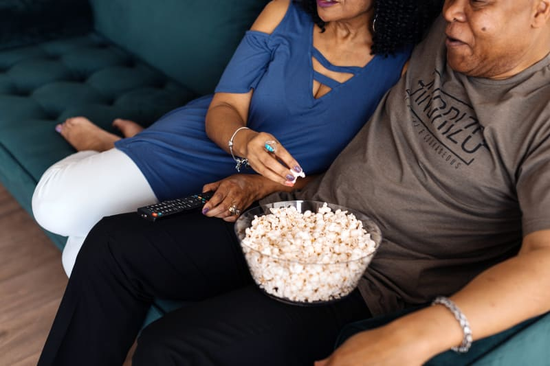 A couple sitting on a couch sharing a bowl of popcorn.