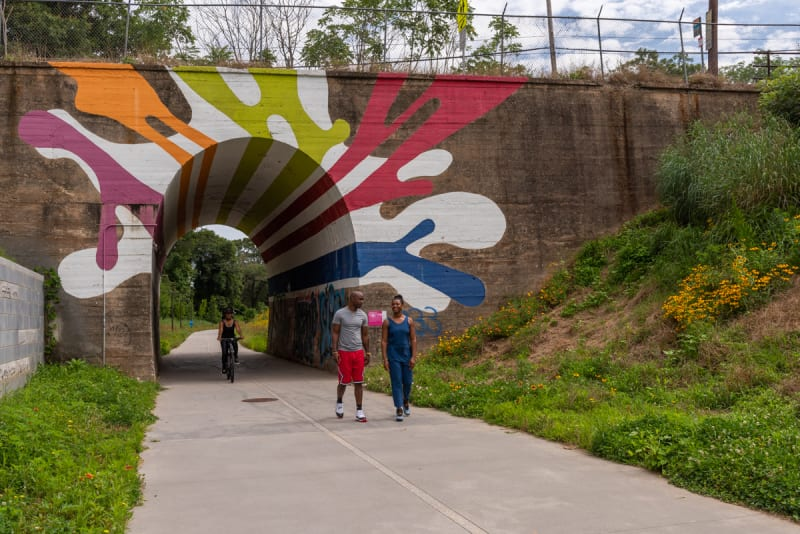 Colorful tunnel mural on Atlanta Beltline Westside Trail with couple walking