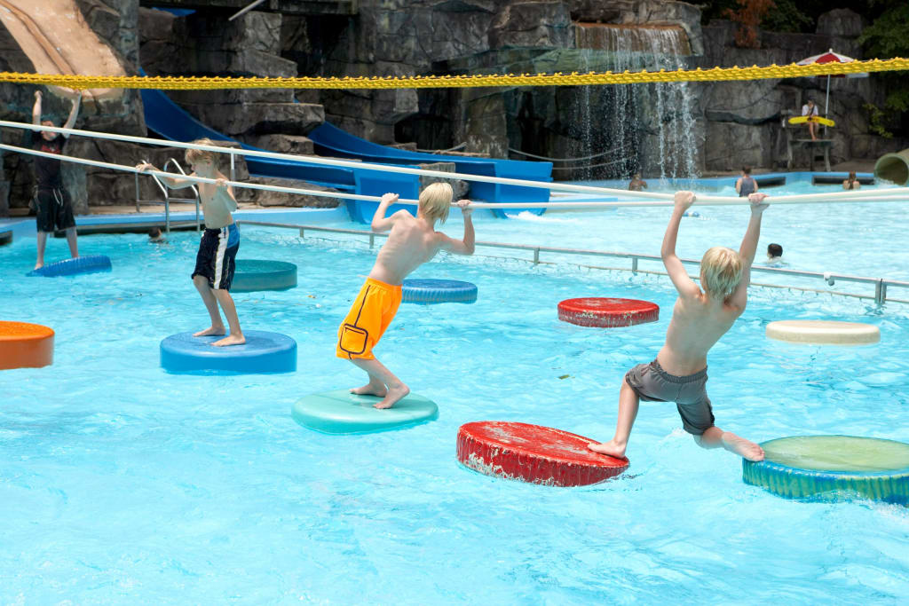 Kids walking across Six Flags White Water floating pads.
