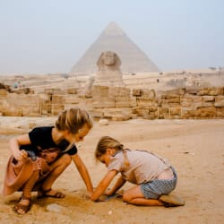 Casually playing in the sand in front of the Sphynx and Giza Pyramids