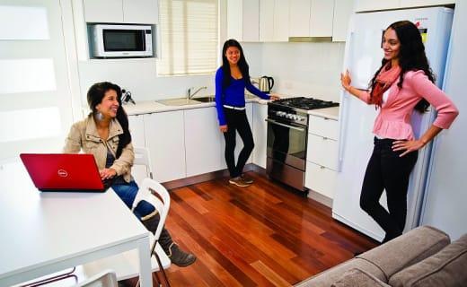Tři studentky stojí společně v kuchyňi