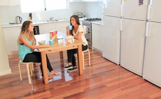 Dvě kamarádky sedí u jídelního stolu