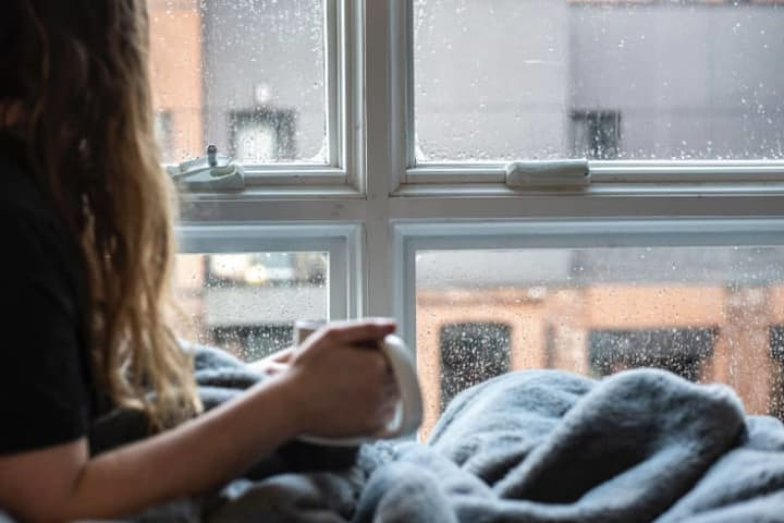Tea time seo, girl looking out of a window on a rainy day